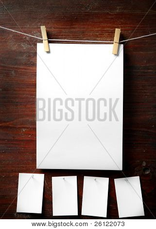 Photo paper attach to rope with clothes pins on wooden background