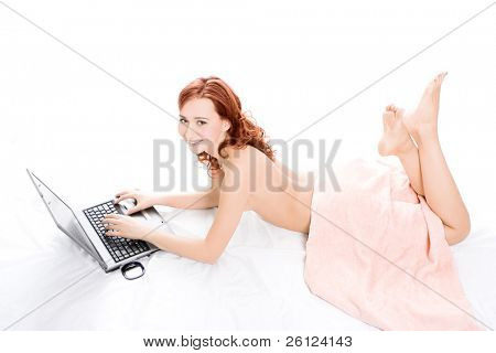 spa naked red beautiful girl lays on white covered by a pink towel and works on laptop