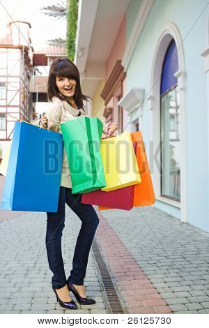 young woman with multi-coloured bags with purchases