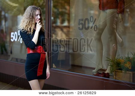 young woman look in shop windows with sale