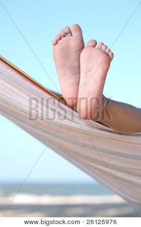 child legs on hammock at sea beach