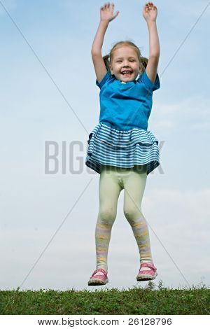 little girl jump om grass under sky