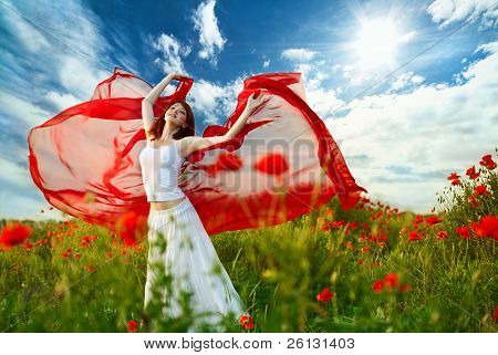 beauty woman in poppy field with red tissue under sky