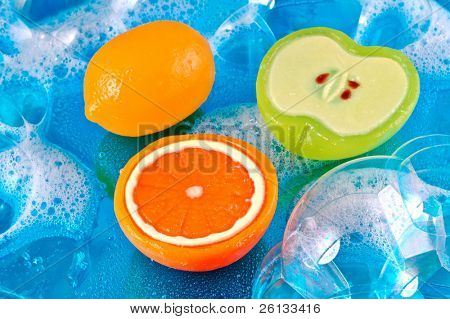 Three soaps in the shape of a lemon, orange, and apple in soap bubbles on a shiny watery blue background