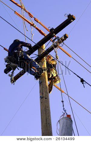 Sichern von Stromleitungen auf einer neuen Kraft-Stange als die Sonne untergeht hinter ihnen zwei Elektriker