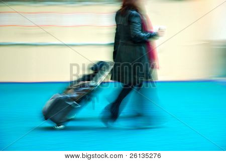 Female traveler rushing through an airport terminal