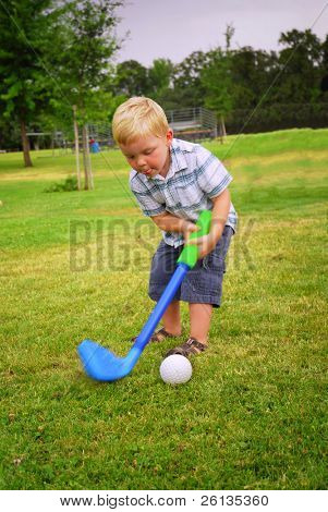 Caucasian toddler playing at park with toy golf club