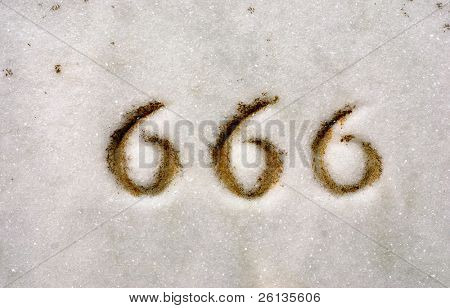 Macro of numbers 666 engraved on granite headstone