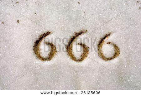 Macro of numbers 666 engraved on granite headstone