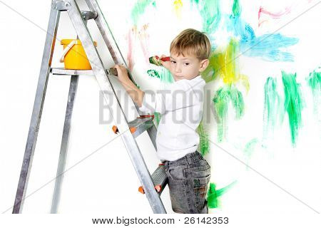 cute young boy painting over white