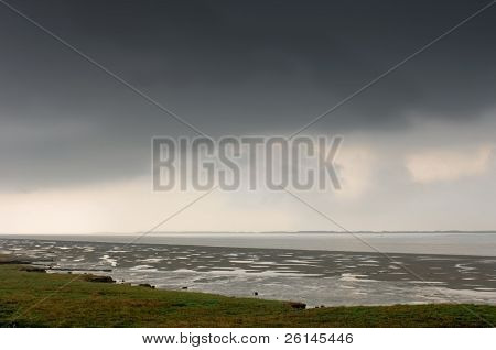 A thunderous sky over the Wester Schelde at low tide in Zeeland, the Netherlands
