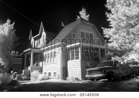 An infra-red photo of a suburban residence with and old pick up truck in the drive way, giving it an appearance of a ghost house