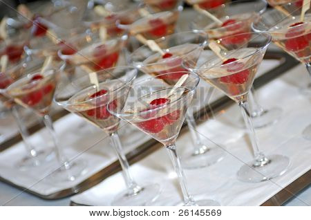 Lines of glasses filled with champagne and two raspberries on a stick, photographed with a shallow depth of field