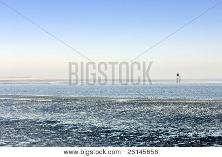 A beacon in the Westerschelde, the Netherlands at low tide on a clear winter day