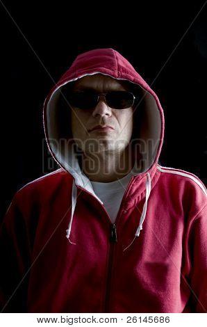 A grim looking Hoodlum wearing sunglasses, and looking mean