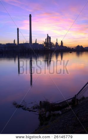 An oil refinery, situated in a commercial harbor, during a radiant sunset. HDR  image