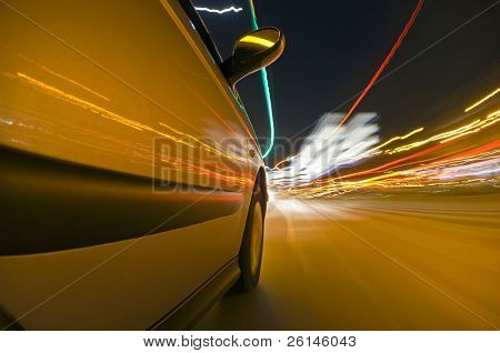 The side of a car, driving at high speed through urban streets, with the various lights passing by, reflecting in the bodywork