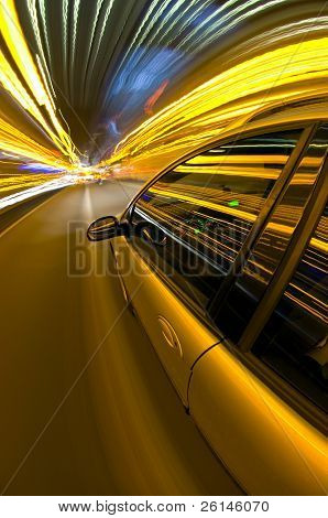 A car racing along a motorway, surrounded by streaks of light of overhead street lights and route information