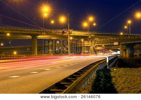 Cars, racing past a huge highway junction at night