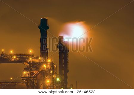Nightly scene of an industrial plant with huge flaring stacks