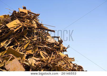 Metal scrap heap detail against a clear blue sky