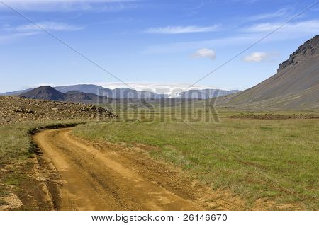 A jeep track or dirt road in Iceland leading around the Hlodufell Volcano winding around remnants of volcanic eruptions, with a clear view of the Langjokull glacier in the distance