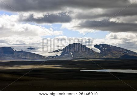 The barren tundra of the Sprengisandur Highlands in Iceland, with the dominating Vatnajokull glacier in the background