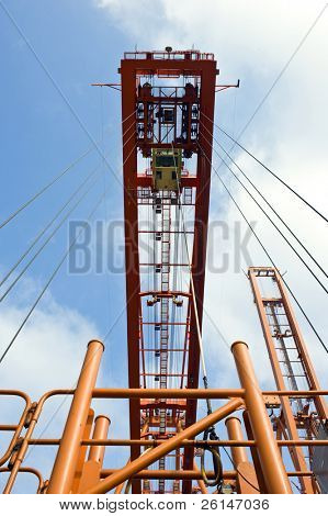 The hoisting rig, used to haul containers at an industrial harbor, with the wires leading up to a huge crane