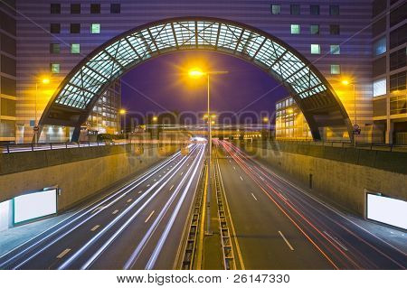 An inner city highway at night with an office building, bridging the traffic