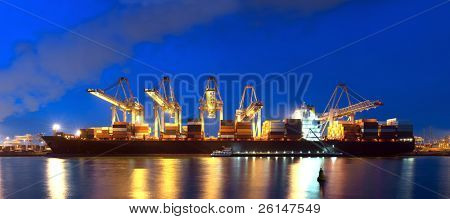 An XXXL file of a container ship being unloaded at night at a busy commercial harbour, with a small trawler moored alongside.