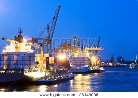 Activity of loading and unloading of huge container ships in a commercial harbor, with a city skyline in the background at dusk
