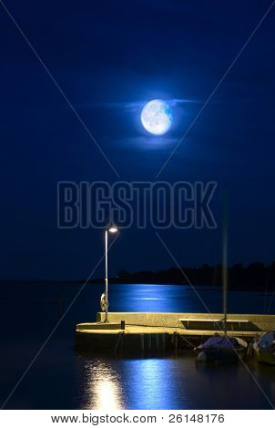 Rising moon over a tranquil harbor pier