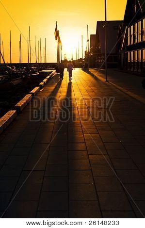 Long shadows on a marina promenade on a summer evening