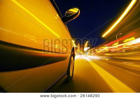 The exterior of a car driving through an urban envrionment, with streaks of light passing by