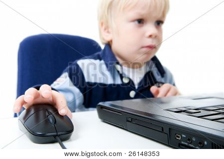A young boy sits using a laptop computer. He is viewable from the chest up, looking away from the camera, and the focus is on the laptop and mouse. Horizontally framed shot.