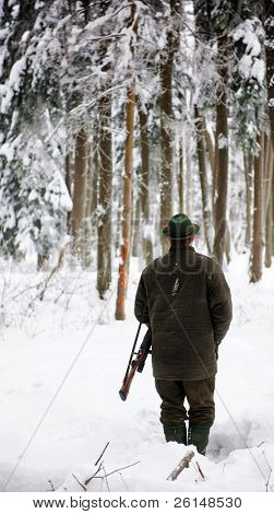 Hunter, armed with a rifle, standing in a snowy forest