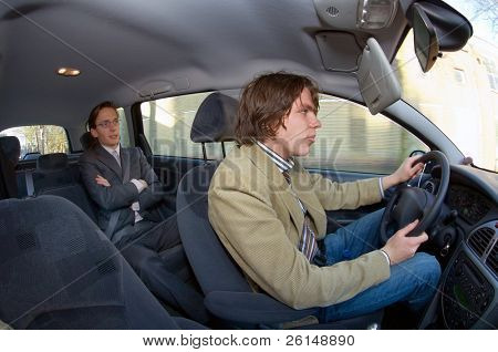 A businessman in the backseat of a taxi, driving through an urban area