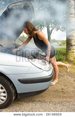 Young woman bending over the blown engine of her car, looking at the oil, whilst smoke is coming from under the hood