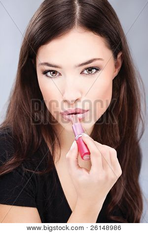 woman putting lipstick on her lips