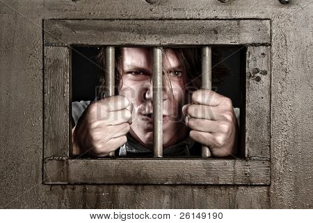 Cross Processed image of a man in prison holding the bars of his cell door.