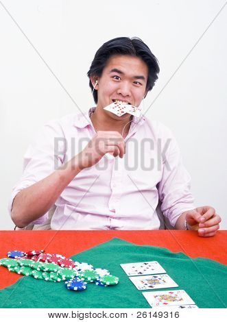 A frustrated poker player biting his cards after loosing an all in game
