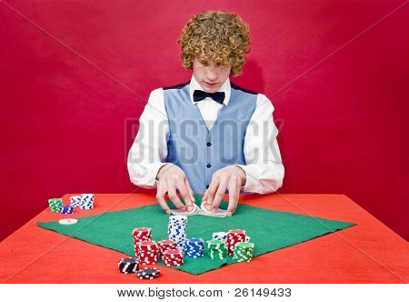 A dealer shuffling cards at a poker table