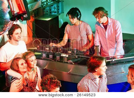 Two disc jockeys at work in the DJ booth at a club