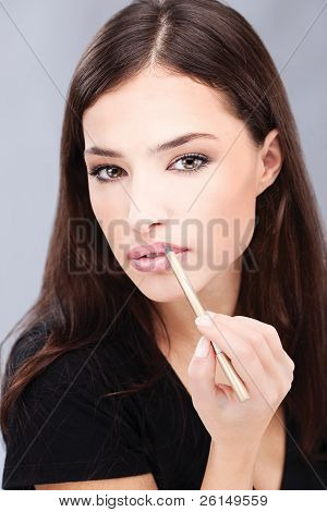 Woman applying cosmetic pencil on her lips