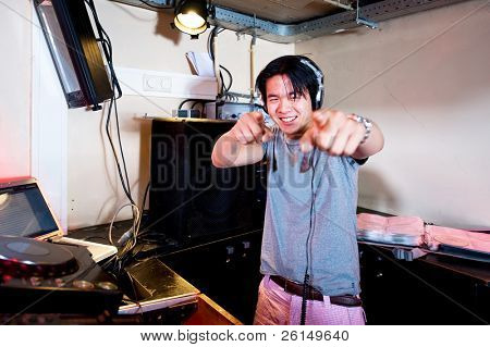 A Dj in a dj booth smiling and pointing at the camera