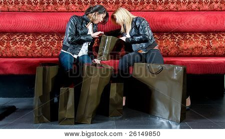 Two young women looking at their newly bought articles while taking a rest on a couch.