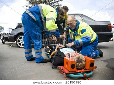 firefighter and paramedic stabilize a victim.