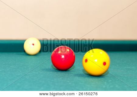 Three billiard balls, used for caroms or carambole on a table, with selective focus on the red ball