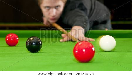 Snooker player placing the cue ball for a shot on black, whilst hitting the red ball (Selective focus and motion blur)