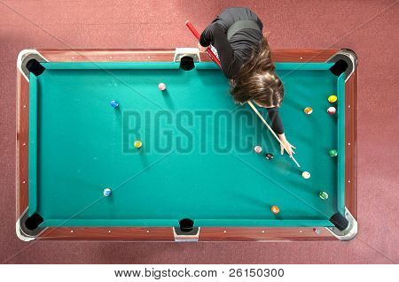 Pool table with a girl playing, seen from above
